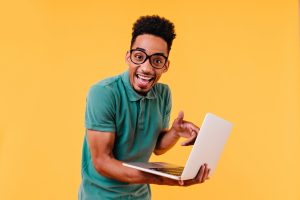 blithesome student green t shirt posing with laptop indoor photo amazed male freelancer isolated